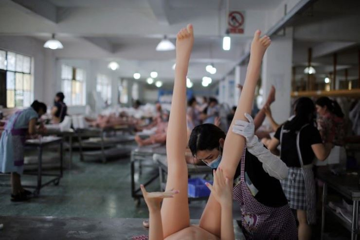 In this July 11, 2018, file photo, workers assemble sex dolls at the WMDOLL factory in Zhongshan, Guangdong Province, China. Reuters