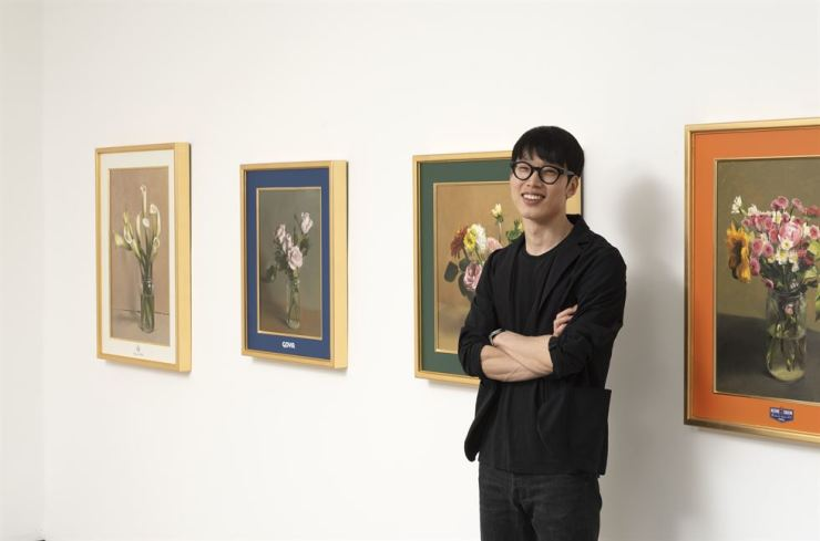 Kim Sung-yoon poses for a photo in front of his paintings at Gallery Hyundai in central Seoul. Courtesy of Gallery Hyundai