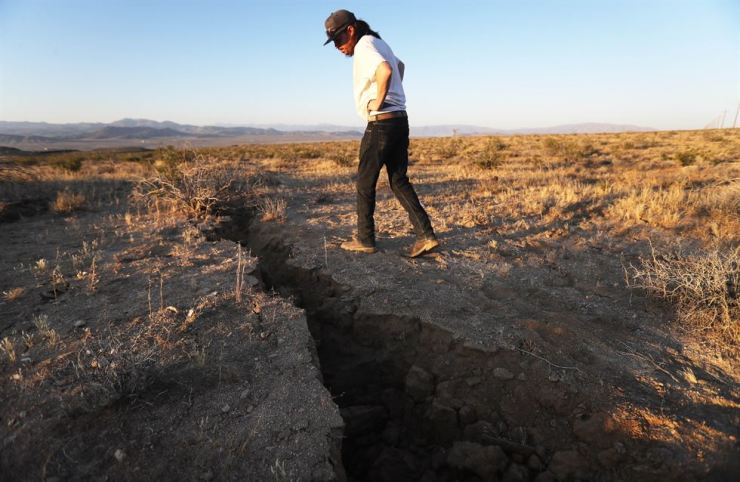 A local resident inspects a fissure in the earth after a 6.4 magnitude earthquake struck the area on July 4, 2019 near Ridgecrest, California. The earthquake was the largest to strike Southern California in 20 years with the epicenter located in a remote area of the Mojave Desert. /AFP-Yonhap