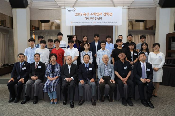 Woongjin Foundation Chairman Shin Hyon-ung, front row fifth from left, poses for a photo with the foundation's high school and university scholarship students and scholars who became their 'mentors of the day' after a mentoring session at the Korea Press Center, Saturday. The mentors in the front row included former Culture Minister Lee O-young, fourth from left, Seoul National University emeritus professor of math Kim Do-han, third from right, and the University of Oxford's math professor Kim Min-hyong, second from right. / Courtesy of Woongjin Foundation