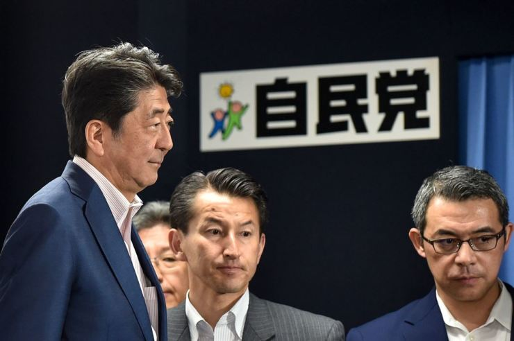 Japanese Prime Minister and ruling Liberal Democratic Party (LDP) president Shinzo Abe (L) leaves after television interviews on the Parliament's upper house election at the party's headquarters in Tokyo on July 21, 2019. (Photo by Kazuhiro NOGI / AFP)