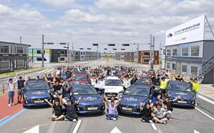 Participants of the 2019 Hyundai Motor Group Autonomous Vehicle Competition for university students pose at a self-driving car testing ground in Hwaseong, Gyeonggi Province, Wednesday. Twelve teams comprised of university students have been developing self-driving cars since April last year and their vehicles will be tested for how quickly they can finish six tasks. The group will pay out a total 200 million won to winners of the competition. Courtesy of Hyundai Motor