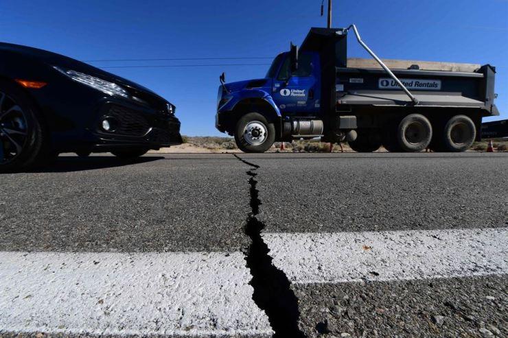 Vehicles drive over a crack on Highway 178 south of Trona, after a 6.4 magnitude earthquake hit in Ridgecrest, California., Thursday. 목요일 규모 6.4의 강진이 캘리포니아 리지크레스트를 강타하며, 트로나 남쪽 178번 고속도로에 생긴 균열 위로 차들이 지나가고 있다. /AFP-Yonhap