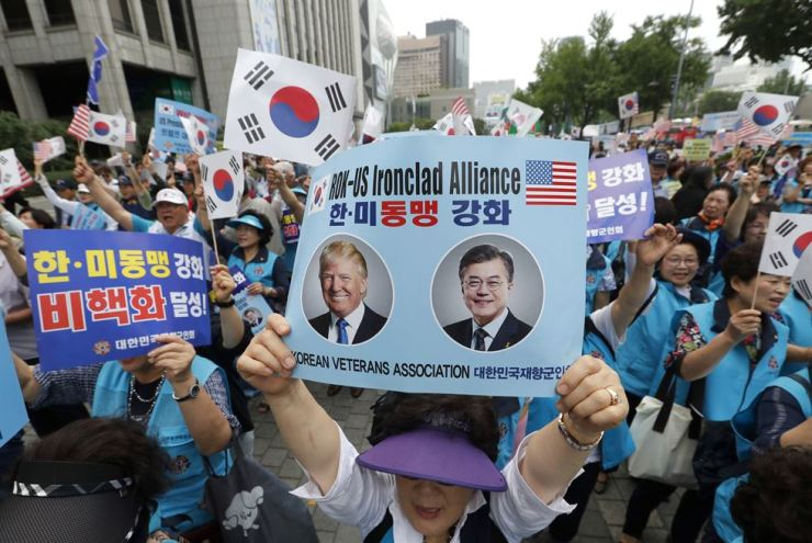 A member of the Korean Veterans Association holds a card showing images of U.S. President Donald Trump and South Korean President Moon Jae-in during a rally to welcome Trump's visit to Seoul on June 30. Trump's drastic North Korea policy shift over the past two years has confused conservatives and liberals in South Korea because it challenges their traditional ideological lines. AP