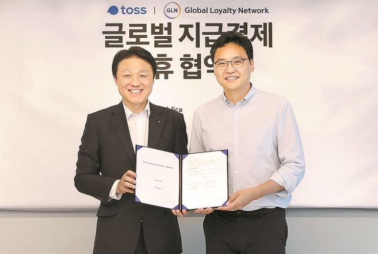 KEB Hana Bank Deputy President and Chief Future Innovation Officer Han Jun-seong, left, poses with Viva Republica CEO Lee Seung-gun after the two signed an agreement, Wednesday, to incorporate the Viva Republica-operated mobile money transfer app Toss into the bank's global payment system. / Courtesy of KEB Hana Bank