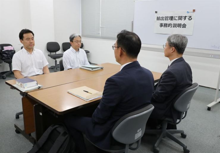 Working level officials from Japan, left, and South Korea hold a meeting about Japan's recent restrictions on exports of high-tech material to South Korea in Tokyo, Japan, Friday. Reuters-Yonhap