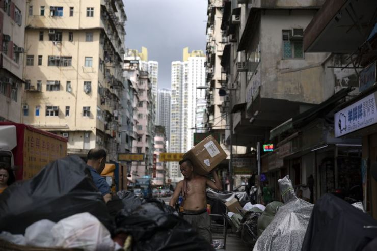 Sham Shui Po, with the high population rate of migrants from mainland China, has long been left behind in Hong Kong's land development. Economic, cultural polarization due to a cultural gap and communication barrier between Hong-Kong residents and the migrants has been dividing the citizens there. One of the poorest districts, Sham Shui Po mirrors the city's social gap between rich and poor that is one of the world's worst. Above, a man carries a box on Shek Kip Mei Street in Sham Shui Po, Hong Kong, July 4. Korea Times photo by Choi Won-suk