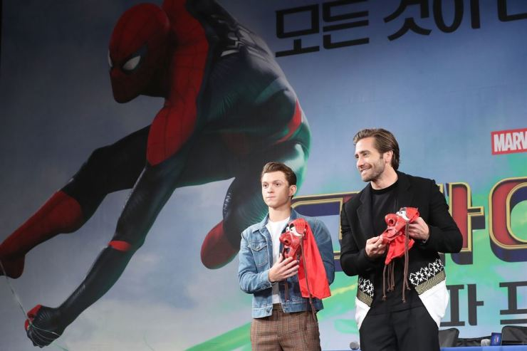 Tom Holland, left, and Jake Gyllenhaal hold Hahoe masks they received as gifts during a press conference for