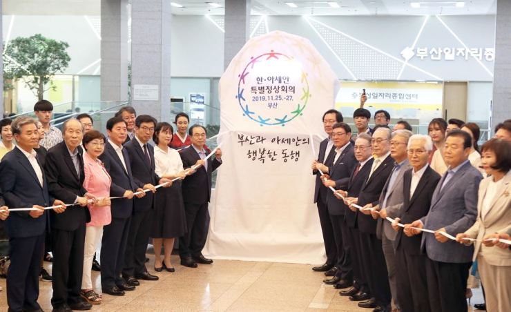 Busan Mayor Oh Keo-don, left of the promotional tower for the 2019 ASEAN-ROK Commemorative Summit, and other officials on Friday celebrated the 100-day countdown to the summit, to be held in the southern port city on Nov 25 and 26. Fifth from left is Suh Jeong-in, executive director of the Summit Preparation Office./ Yonhap