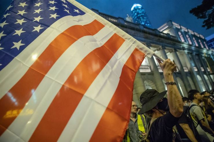 A protester holds up the US flag during an anti-government rally in Hong Kong, China, 16 August 2019. The goal of the rally is to drum up support from the US and UK for the pro-democracy movement in Hong Kong. Hong Kong has been engulfed in protests since early June, at first to oppose the now-suspended extradition bill to China, that have developed into an anti-government movement. EPA/ROMAN PILIPEY