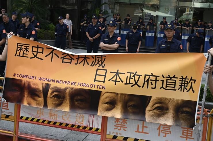 Activists unfurl a banner in front of police calling for the Japanese government to apologize for its role in the wartime sex slavery of so-called 'comfort women' ― forced to work in wartime Japanese military brothels during World War II ― during a demonstration outside the Japan Exchange Association in Taipei, Aug. 14. AFP