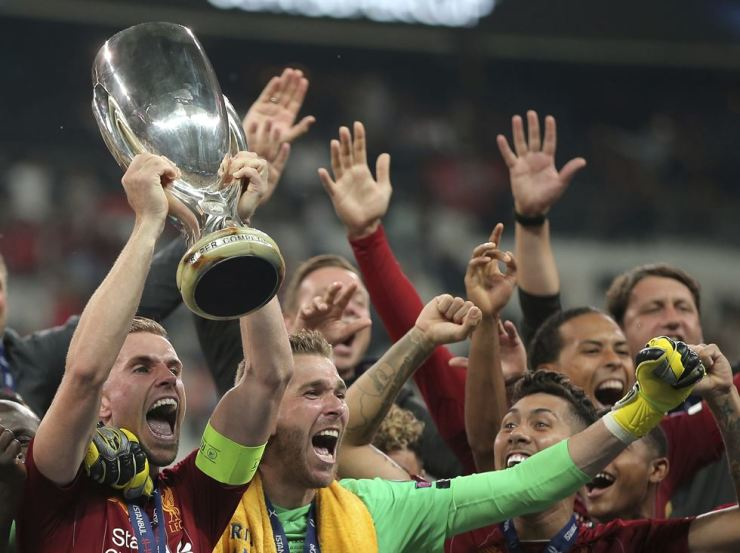 Liverpool's Jordan Henderson lifts up the trophy as he celebrates with teammates after winning the UEFA Super Cup football match against Chelsea in Besiktas Park, Thursday. /AP-Yonhap