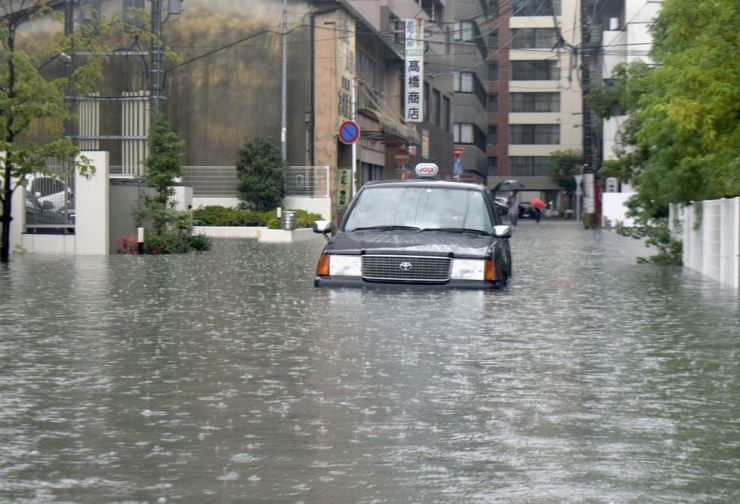 A taxi is stuck in a flooded street in Saga, southern Japan, Wednesday, Aug. 28, 2019. Kyodo News via AP