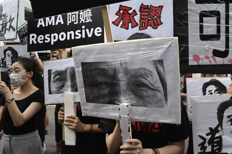 Activists display placards and posters calling for the Japanese government to apologize for its role in the wartime sex slavery of so-called 'comfort women' ― forced to work in wartime Japanese military brothels during World War II ― during a demonstration outside the Japan Exchange Association in Taipei, Aug. 14. AFP