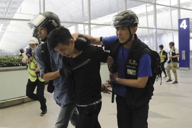 Police arrest a protester during a demonstration at Hong Kong's airport, Tuesday. Riot police moved into the terminal to confront protesters who shut down operations at the busy transport hub for two straight days. (AP Photo/Kin Cheung)