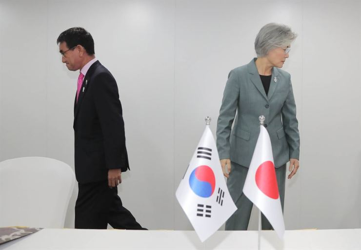 Foreign Minister Kang Kyung-wha and her Japanese counterpart Taro Kono head to their seats after shaking hands ahead of a bilateral meeting on the sidelines of the ASEAN Regional Forum in Bangkok, Thailand, Thursday. Yonhap