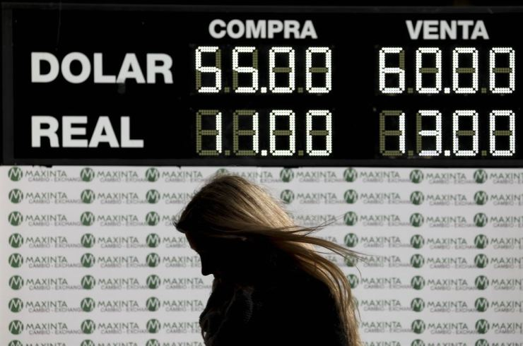 A woman walks past a currency exchange board in Buenos Aires, Argentina, Monday, Aug. 12, 2019. The peso devalued sharply on Monday in Argentina after a striking victory by the opposition in Sunday's presidential primaries ahead of October's presidential primaries ahead of October's presidential elections. AP