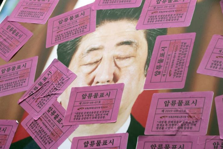 Asset seizure stickers cover a photo of Japanese Prime Minister Shinzo Abe during an anti-Abe protest in front of the Japanese embassy in Seoul, Wednesday. Members of the public servants' union organized the rally. Korea Times photo by Shim Hyun-chul