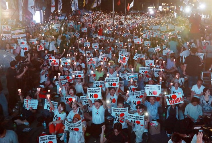 Thousands of protesters take part in a candlelit rally in front of the old Japanese embassy building in Seoul, Saturday, holding placards that read 'We condemn the Abe administration. Apologize for forced labor.' Yonhap