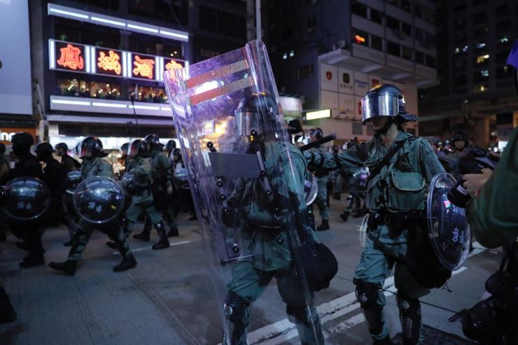 Police officers armed with riots gear walk during pro-democracy protesters march in Hong Kong Saturday, Aug. 17, 2019. Another weekend of protests is underway in Hong Kong as Mainland Chinese police are holding drills in nearby Shenzhen, prompting speculation they could be sent in to suppress the protests. (AP Photo/Kin Cheung)