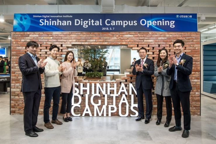 Shinhan Financial Group Chairman Cho Yong-byoung, third from right, applauds with the group's digital experts, during the opening ceremony of Shinhan Digital Campus in Shinhan L Tower in Seoul in this March 2018 file photo. / Courtesy of Shinhan Financial Group