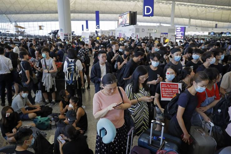 Stranded travelers using smartphones are surrounded by protesters during a protest at the Hong Kong International Airport, Monday, Aug. 12, 2019. One of the world's busiest airports canceled all flights after thousands of Hong Kong pro-democracy protesters crowded into the main terminal Monday afternoon. AP