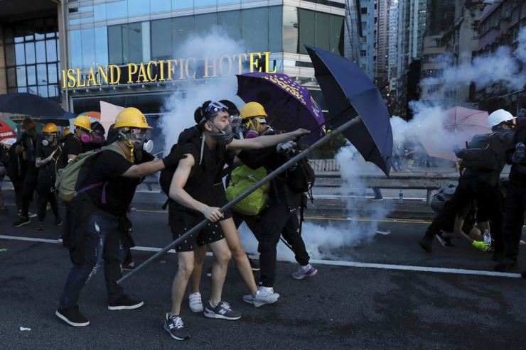 In this July 28, 2019, file photo, protesters use umbrellas to shield themselves from tear gas fired by policemen as they face off on a streets in Hong Kong. AP