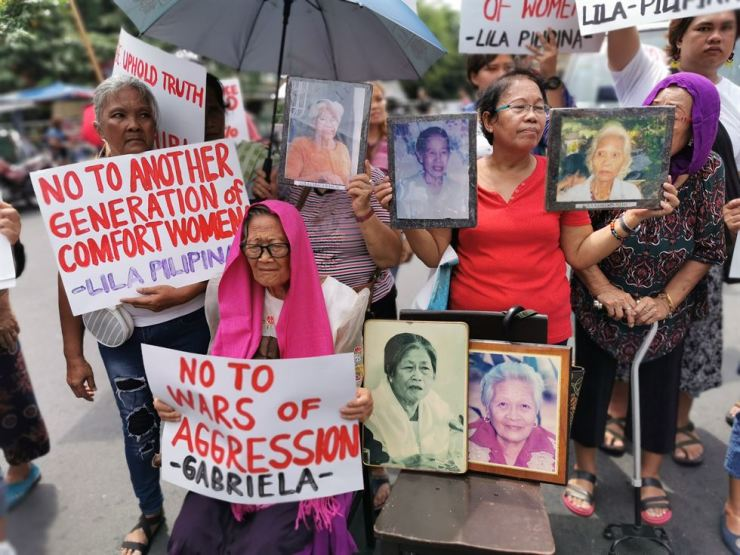 A woman, who claims to be a victim of sexual abuse of the Japanese Imperial Army during World War II, holds a placard as she joins a demonstration marking the International Day to Commemorate Victims of Japanese Wartime Sexual Slavery, near the Malacanang presidential palace in Manila, Philippines, Aug. 14. EPA