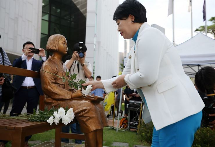 A woman places a chrysanthemum on the statue symbolizing