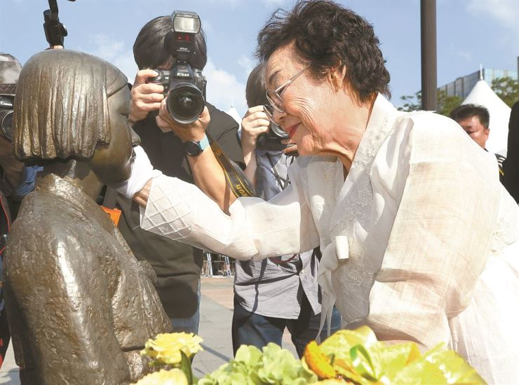 Lee Yong-soo, a victim of Japan's wartime sexual slavery, pats the statue symbolizing