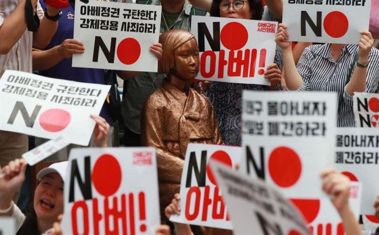 Anti-Abe protesters surround the statue symbolizing
