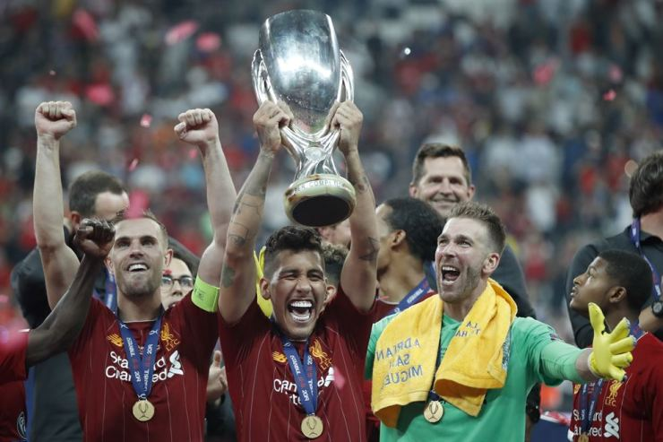 Liverpool's Jordan Henderson, Roberto Firmino and goalkeeper Adrian, from left to right, celebrate with the trophy after winning the UEFA Super Cup soccer match between Liverpool and Chelsea, in Besiktas Park, in Istanbul, Thursday. /AP-Yonhap