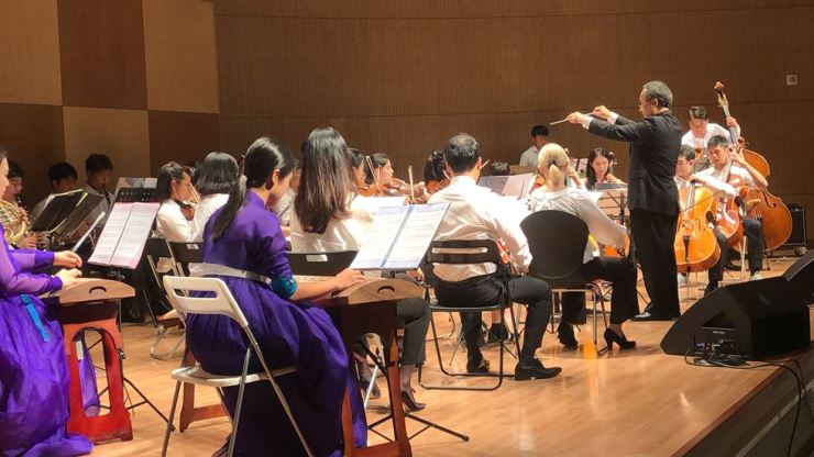 The Lindenbaum Festival Orchestra members perform under the baton of Toshiyuki Shimada, conductor of Eastern Connecticut Symphony Orchestra at an auditorium in the Jeju 4.3 Peace Park, Aug. 7, the second day of the 2019 Lindenbaum Peace Workshop and Concert held in Jeju. Courtesy of Lindenbaum Organization