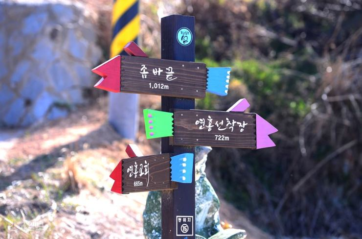 A colorful road sign, top, on Yeonhong Island, South Jeolla Province, shows directions to the wharf, church and the northwest end of the island. The formerly desolate island has transformed into a gigantic art museum with various art pieces and installations. / Korea Times file photo