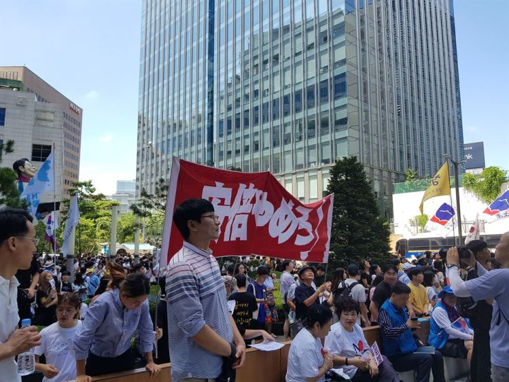 Japanese protesters at Wednesday's rally in Seoul hold up a sign that says