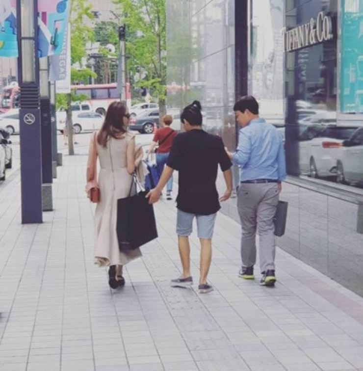 Jolie, left, and her son Maddox Jolie-Pitt walk with a man believed to be their interpreter near Lotte Department Store in central Seoul in this undated photo.