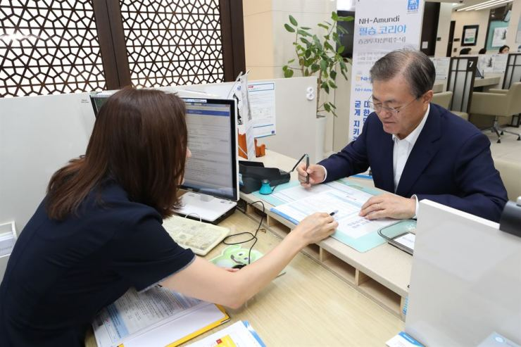 President Moon listens to a bank employee before signing an investment agreement document for a private equity fund set up to nurture local parts and materials exporters at NongHyup Bank's headquarters in Seoul, Aug. 26. Yonhap
