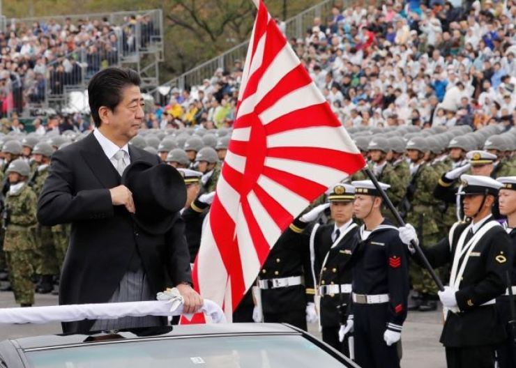 Japanese Prime Minister Shinzo Abe stands next to the Rising Sun Flag during a Japan Self-Defense Forces exercise in Saitama Prefecture in October, 2018. Reuters