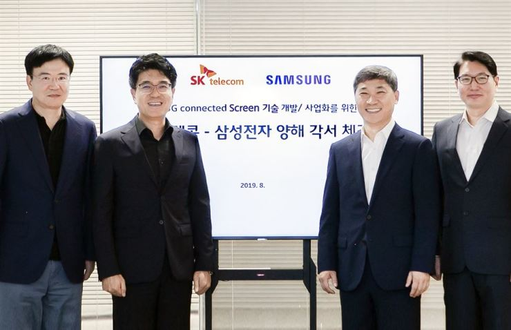 Park Jin-hyo, second from left, who heads SK Telecom's ICT Technology Center, and Lee Hee-man, right, who heads Samsung Electronics' VD Service PM Group, with other officials after signing a MOU to develop 8K TV powered by 5G networks. / Courtesy of SK Telecom