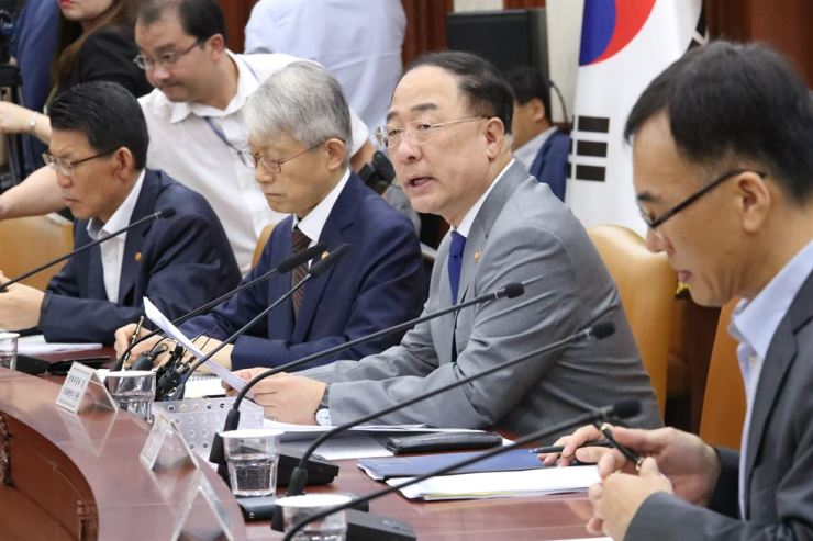 Deputy Prime Minister Hong Nam-ki, second from right, speaks during a meeting attended by economy-related ministries at the Government Complex in Gwanghwamun, Seoul, Sept. 10. The ministers discussed ways to help protect export firms against external uncertainties, innovate contents businesses and grant more people broader investment opportunities for real estate investment trust (REIT) businesses. Yonhap