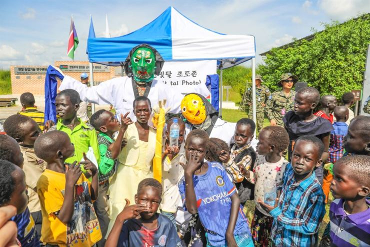 Hanbit soldiers wearing Korean traditional masks and Nuer children pose for a photo during the Hanbit unit's Chuseok event in South Sudan. Courtesy of Hanbit unit