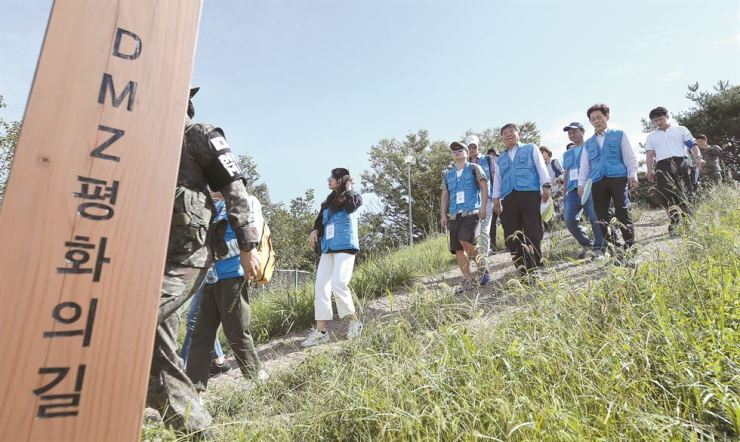 Second Vice Minister of Culture, Sports and Tourism Roh Tae-kang and a special group of foreign students walk a trail along the Demilitarized Zone in Cheorwon, Gangwon Province, Sept, 17, during an event to mark the third inter-Korean summit a year earlier. Thirteen university students from 12 foreign countries including the United States, Britain, Italy, Vietnam and Mexico participated in the three-hour walk at the DMZ Peace Trail. Courtesy of Ministry of Culture, Sports and Tourism