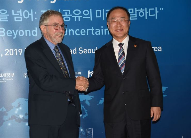 Deputy Prime Minister Hong Nam-ki, right, shakes hands with Nobel Laureate professor Paul Krugman during the 2019 Knowledge Sharing Program (KSP) Dissemination Conference at the Conrad Hotel on Yeouido, Seoul, Monday. / Courtesy of Ministry of Economy and Finance