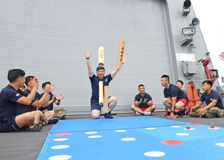 Sailors of the Republic of Korea Navy's Cheonghae unit in the Gulf of Aden play yutnori, a traditional Korean game. Courtesy of Cheonghae unit