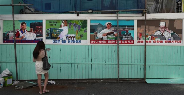 A woman takes a photo of the signs that satirize North Korean-style slogans near the North Korea-themed pub under construction in Seoul's Hongdae area, Sept. 16. Yonhap