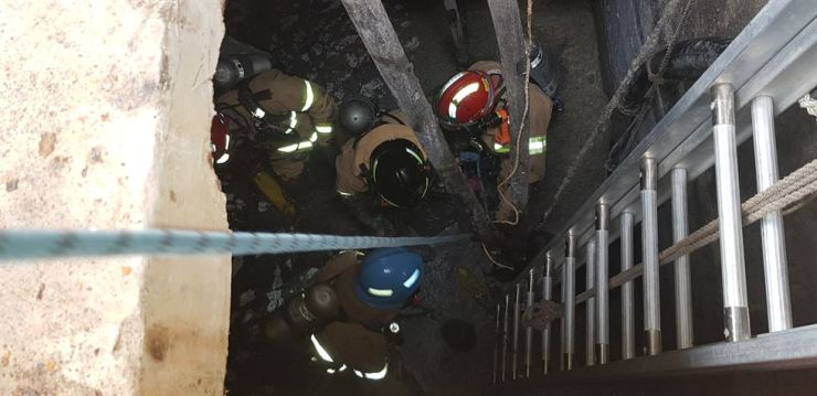 Rescue workers carry out relief work inside an underground tank at a fishery products processing factory in Yeongdeok, North Gyeongsang Province, Wednesday. Yonhap