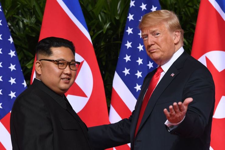 In this file photo taken on June 12, 2018, U.S. President Donald Trump, right, meets with North Korea's leader Kim Jong-un at the start of their summit at the Capella Hotel on Sentosa Island, Singapore. AFP