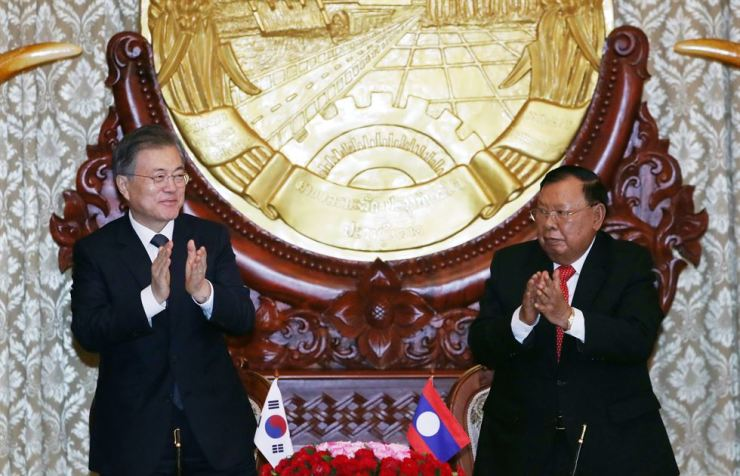President Moon Jae-in, left, and Laotian President Bounnhang Vorachith celebrate after signing a memorandum of understanding between South Korea and Laos following a summit at the presidential palace in Laos, Thursday. Yonhap