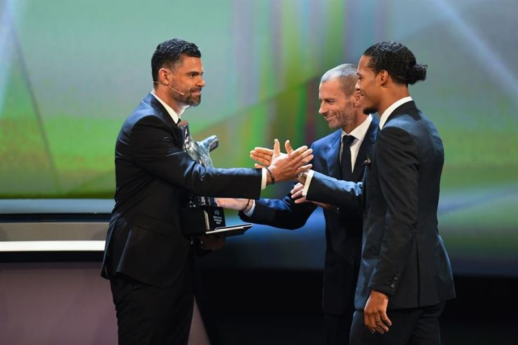 Virgil Van Dijk of Liverpool FC receives the Player of the Year award from UEFA President Aleksander Ceferin and host Pedro Pinto during the UEFA Champions League 2019-20 Group Stage draw ceremony in Monaco, 29 August 2019. /EPA-Yonhap