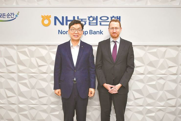 NongHyup Bank CEO Lee Dae-hoon, left, poses for a photo with Austrade North East Asia General Manager Brett Cooper, at the bank's headquarters in Seoul, Sept. 10. Courtesy of NongHyup Bank
